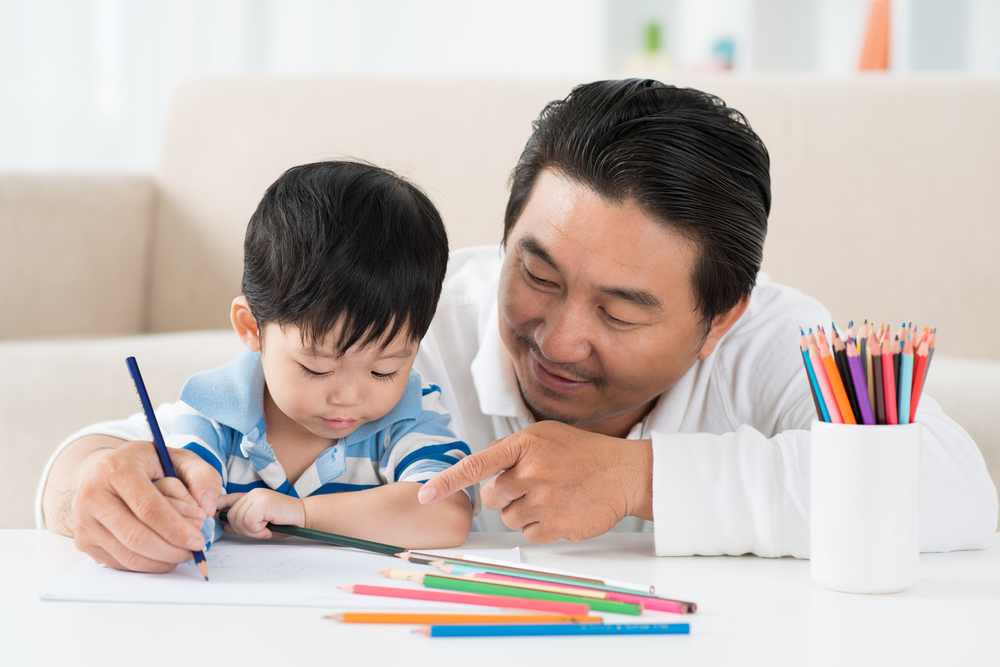 Father teaches son coloring, that helps with fine motor skills too.