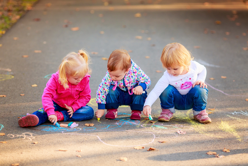 Toddlers Drawing Outside with a chalk on a sidewalk