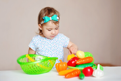 girl playing with plastic fruits