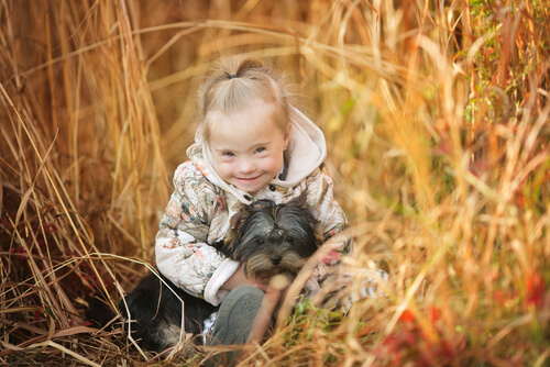 girl with down syndrome playing with her dog