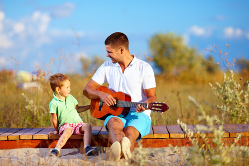 Father playing guitar to his child unschooling